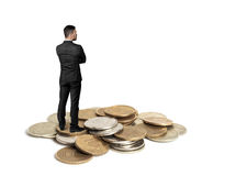 Cutout businessman with folded arms standing on a copper heap of ruble coins Royalty Free Stock Photos