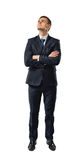 Cutout businessman stands with folded arms looking up. stock photography