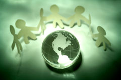 Cutout figures around globe. A view of a row of paper cutout figures holding hands around a glass globe of the world. World unity and peace theme royalty free stock photography
