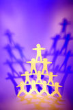 Cutout figures in pyramid. A pyramid formed by different levels of cutout people figures, each supporting the level above.  Themes;  Team support, collaboration Stock Photography