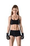 Cutout fitness model wearing sportswear stands looking directly at the camera, holding dumbells. Stock Photo