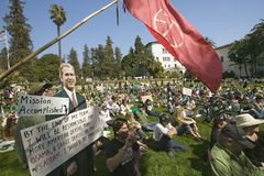A cutout of George W. Bush saying Mission Accomplished is seen with a crowd of protesters and a red peace flag at an anti-Iraq War Stock Photos