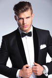 Cutout photo of business man holding his jacket. Cutout picture of an elegant young fashion man holding both hands on his tuxedo jacket while looking at the royalty free stock photos