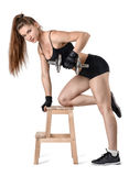 Cutout portrait of muscular young woman lifting a dumbbell for training her back muscles leaning on the chair Stock Image