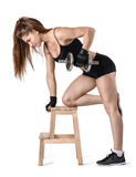 Cutout portrait of muscular young woman lifting a dumbbell for training her biceps leaning on the chair Stock Photos