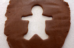 Cutout shape of a gingerbread man in cookie dough Stock Photos