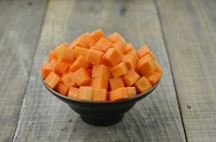 Cuts cubes of carrot in black bowl on wooden table. Cuts cubes of carrot in black bowl on wooden background Royalty Free Stock Photos