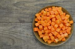 Cuts cubes of carrot in black plate on wooden background. Cuts cubes of carrot in black plate on wooden table Royalty Free Stock Photography