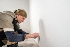 Cuts holes in Wallpaper for electrical outlets. Young man, worker glueing wallpapers on concrete wall. Repair the. Young man, worker glueing wallpapers on stock photo