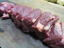 Cuts of lean beef meat on a clean wooden board Royalty Free Stock Images