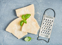 Cuts of Parmesan cheese with metal grater and fresh basil over concrete textured background. Top view stock image