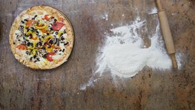 Cuts the pizza on a dark background in the kitchen stock images