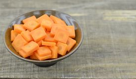 Cuts slices carrots in black bowl on wooden table. Closeup Stock Photo