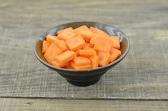 Cuts slices carrots in black bowl on wooden table. Closeup Stock Images
