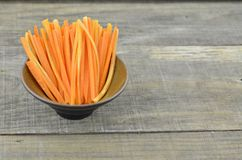 Cuts stick carrots in black bowl on wooden table, closeup. Cuts stick carrots in black bowl on wooden table Royalty Free Stock Photo
