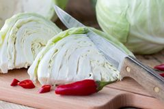 Cutted cabbage on cutting board. With red chili peppers and knife on wooden background Stock Images
