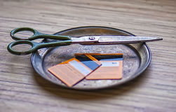 Cutted credit card, scissors, insolvent client, no money. Color photo of a pair of scissors lying on a metal plate with cutted to halfs invalid orange credit Stock Image