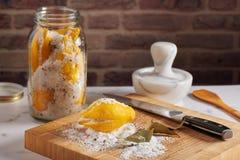 Cutted cytryna w mieszanki morza pikantność, soli, słój z solonymi cytrynami i moździerz na za ściany z cegieł tłem i, fotografia stock