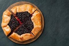 Cutted galette用季节性莓果 舱内甲板在背景的被放置的酥脆夏天莓果饼与拷贝空间 库存图片