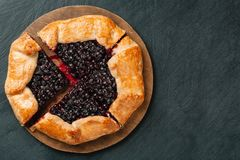 Cutted galette with seasonal berries. Flat lay crispy summer berry pie on a background with copy space stock images