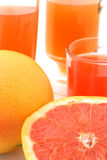 Cutted grapefruit and his juice. Cutted grapefruit with three glass of grapefruit juice on background Stock Photography