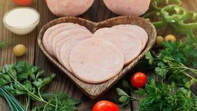 Cutted Ham Sausage na placa do coração no fundo de madeira fotos de stock royalty free