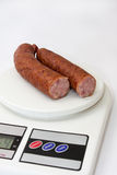 Cutted homemade smoked sausage on a kitchen digital scale Stock Image