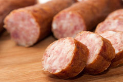 Cutted homemade smoked sausage on a kitchen wooden board Stock Image