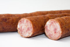 Cutted homemade smoked sausage on a white background Stock Image