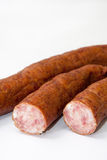 Cutted homemade smoked sausage on a white background Stock Images