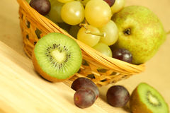 Cutted kiwi and fruits basket Royalty Free Stock Images