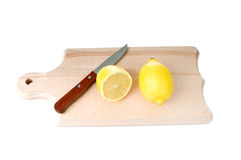 Cutted lemon and knife on wooden plank. One whole lemon and one cut lemon with knife on wooden plank. Isolated on white background Stock Photography