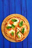 Cutted margherita pizza with basil on blue background with copys Royalty Free Stock Photo