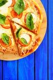 Cutted margheritapizza med basilika på blå bakgrund med copys Royaltyfria Foton