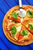 Cutted margheritapizza med den rund kniven och basilika Royaltyfria Foton