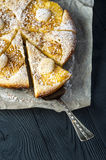 Cutted pineapple pie on baking paper with scapula Royalty Free Stock Photo