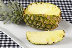 Cutted pineapple. A cutted pineapple on a porcellain plate. The plate is located on a black-white checkered tablecloth Royalty Free Stock Photos