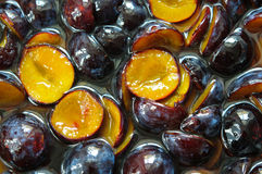 Cutted plums in sugar syrup. Cutted dark and yellow plums in sugar syrup Royalty Free Stock Photo