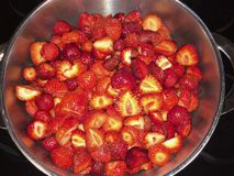 Cutted and sugared fresh red strawberrys in a cooking pot to make homemade marmalade. Shine strawberry fruits in a cooking pot with sugar prepared to cook a royalty free stock photos