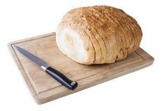 Cutted vitt bröd på det wood brädet med kniven Arkivbild