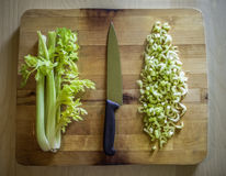 Cutted and whole celery on a wooden board with a knife. In the middle Stock Images
