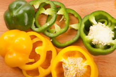 Cutted yellow and green bell peppers on cutting board Stock Photo