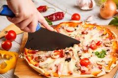 Cutter cuts a fresh pizza Stock Photos