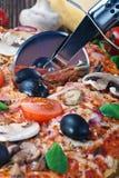 Cutter cuts a fresh pizza Stock Photo