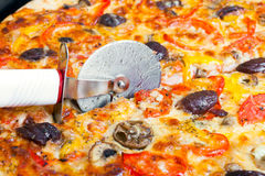 Cutter cuts a pizza Stock Photos