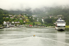 Cutter floats to shore with coastal village Stock Photo
