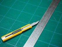 Cutter and iron ruler isolated on a cutting mat stock images