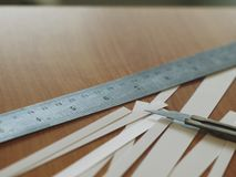 Cutter knife with stainless ruler and strip of white paper Stock Photography