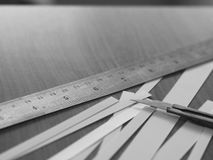 Cutter knife with stainless ruler and strip of white paper Royalty Free Stock Images