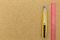 Cutter and ruler on cork board Stock Image